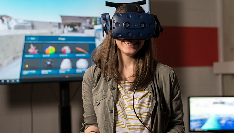 A smiling young woman wearing a virtual reality headset stands in front of a display screen.