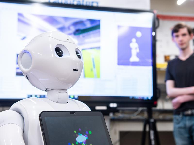 An all-white robot with a very rounded head has a computer screen on its chest.  It is looking very attentively at someone outside the picture frame.  A student stands off to the side watching.